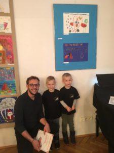 Zdjęcie przedstawia dwóch chłopców w wieku przedszkolnym. Uśmiechnięci stoją przy ścianie, obok nich kuca młody mężczyzna.