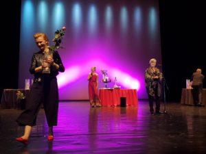 Zdjęcie przedstawia kilka osób na scenie. Najprawdopodobniej trwa uroczystość wręczenia nagród, ponieważ na scenie ustawione są stoły z pucharami i kwiatami. Na pierwszym planie ze sceny schodzi kobieta, w rękach trzyma puchar i różę.