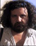 Zdjęcie przedstawia mężczyznę. Ma brodę i włosu do ramion.