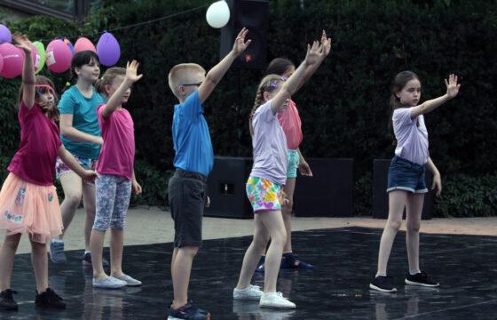 Zdjęcie przedstawia grupę dzieci tańczących na świeżym powietrzu. Za nimi zawieszone są balony.