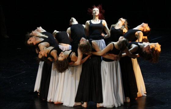 Grupa młodych tancerze na scenie, stoją ciasno spleceni w okręgu, głowy odchylone do tyłu