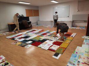 Kobieta i dwóch mężczyzn oglądają prace plastyczne rozłożone na podłodze. Mają maseczki na twarzy.