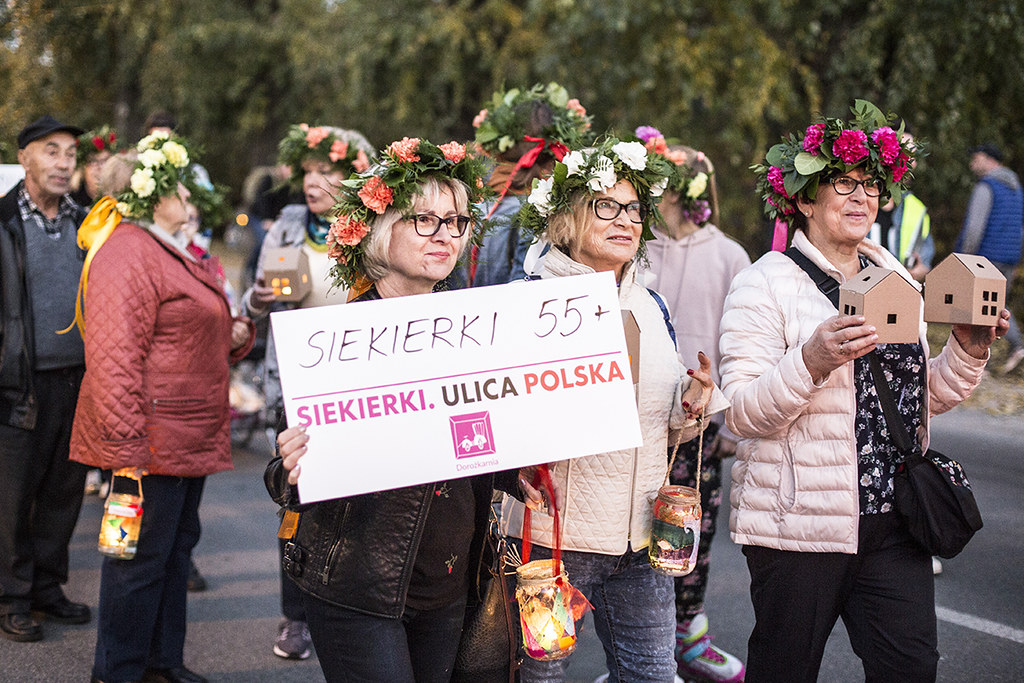 Grupa kobiet na ulicy. Mają wianki z kwiatów na głowie. Jedna trzyma planszę z napisem Siekierki 55+