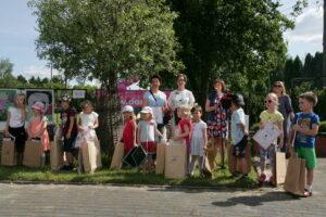 Zdjęcie przedstawia grupę dzieci w wieku przedszkolnym. Stoją na podwórku, jest lato - dzieci są w koszulkach z krótkim rękawem i krótkich spodenkach.