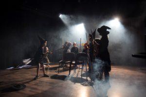 Zdjęcie przedstawia scenę z przdstawienia teatralnego. Na scenie są dziewczynki przebrane za czarownice.