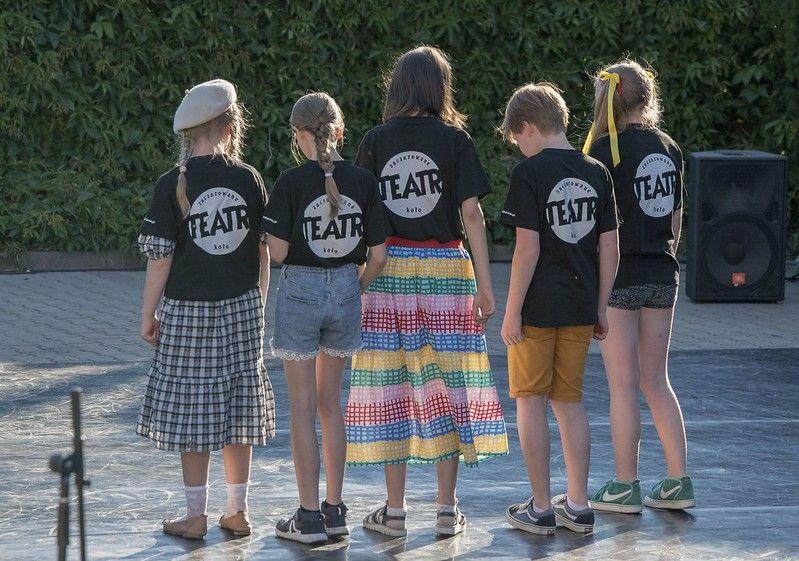 4 dziewczynki i jeden chłopiec stoją tyłem do kadru, wszyscy w koszulkach z napisem na plecach - Teatr Zaczarowane Koło. Zdjęcie wykonano w plenerze