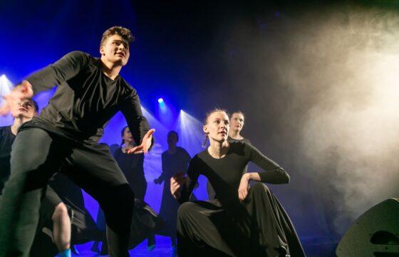 Zdjęcie przedstawia grupę tancerzy na scenie. na pierwszym planie chłopak i dziewczyna.