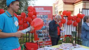 """Stoisko promocyjne """"Gazety Siekierkowskiej"""", na stole leżą egzemplarze gazety, stoisko jest udekorowane balonami i zdjęciami."""