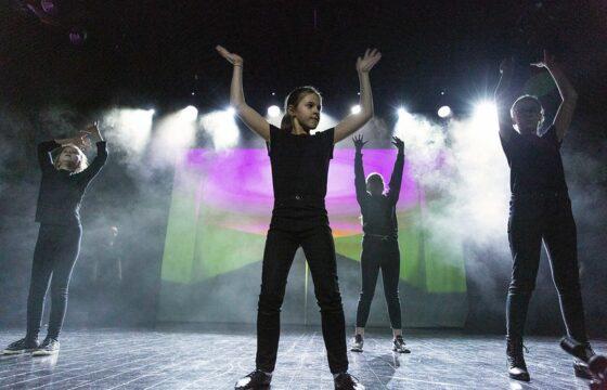 Grupa dziewcząt na scenie, w jednakowych kostiumach: spodniach i podkoszulkach.