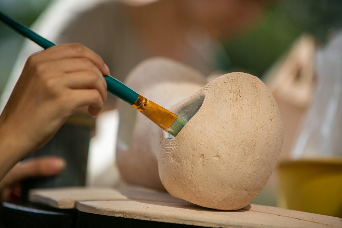 Dłoń z pędzlem, maluje naczynie ceramiczne.