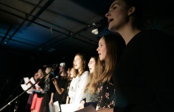 Zdjęcie przedstawia grupę młodzieży na scenie. Stoją przed mikrofonami. Najprawdopodobniej śpiewają.