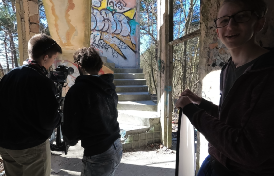 Trójka młodych mężczyzn, w ruinach budynku. Ustawiają kamerę. Plan filmowy