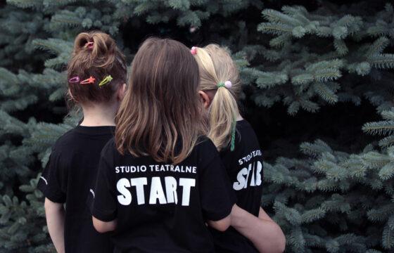 Zdjęcie przedstawia trzy dziewczynki. Są odwrócone plecami do kadru. Mają koszulki z napisem Studio Teatralne Start.