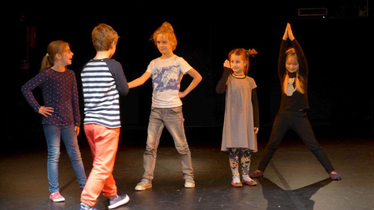 Zdjęcie przedstawia pięcioro dzieci na scenie. Wyglądają jakby odgrywali jakąś scenkę. Wśród dzieci są dwaj chłopcy i trzy dziewczynki.