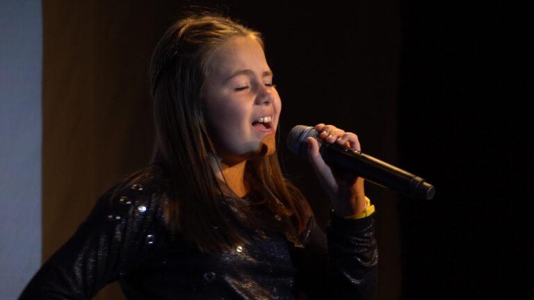 Zdjęcie przedstawia dziewczynę, która trzyma mikrofon w ręce.