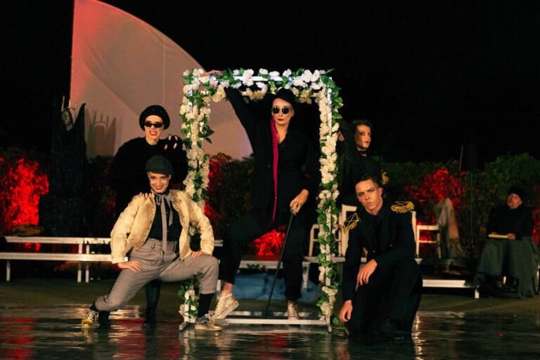 Grupa młodych ludzi na scenie. Kostiumy i scenografia wskazują na spektakl