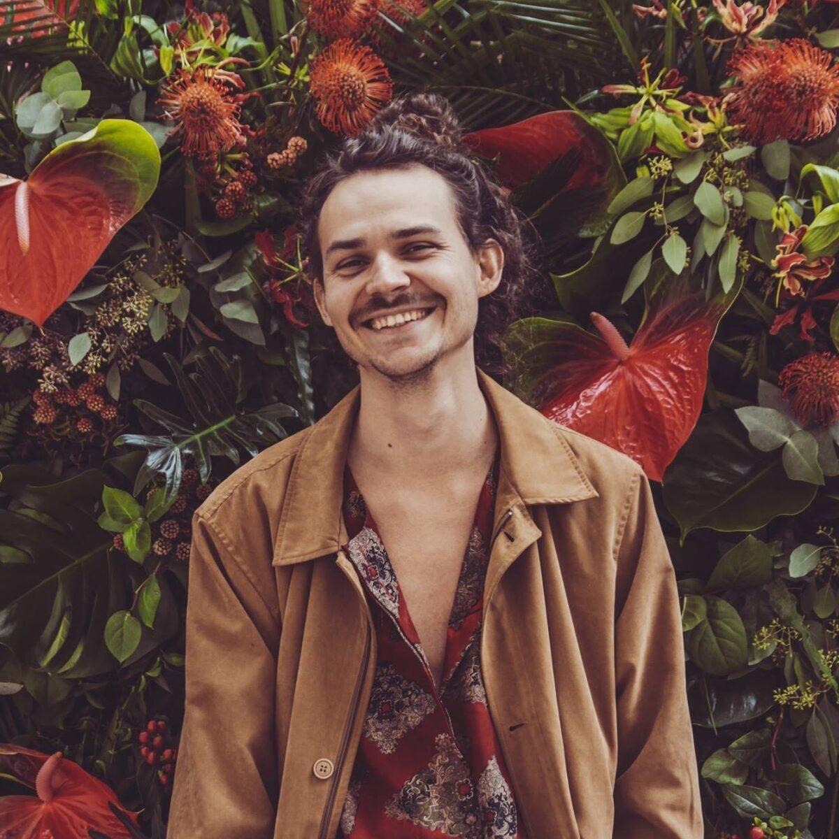zdjęcie przedtawia młodego, uśmiechniętego chłopaka na tle kwiatów.