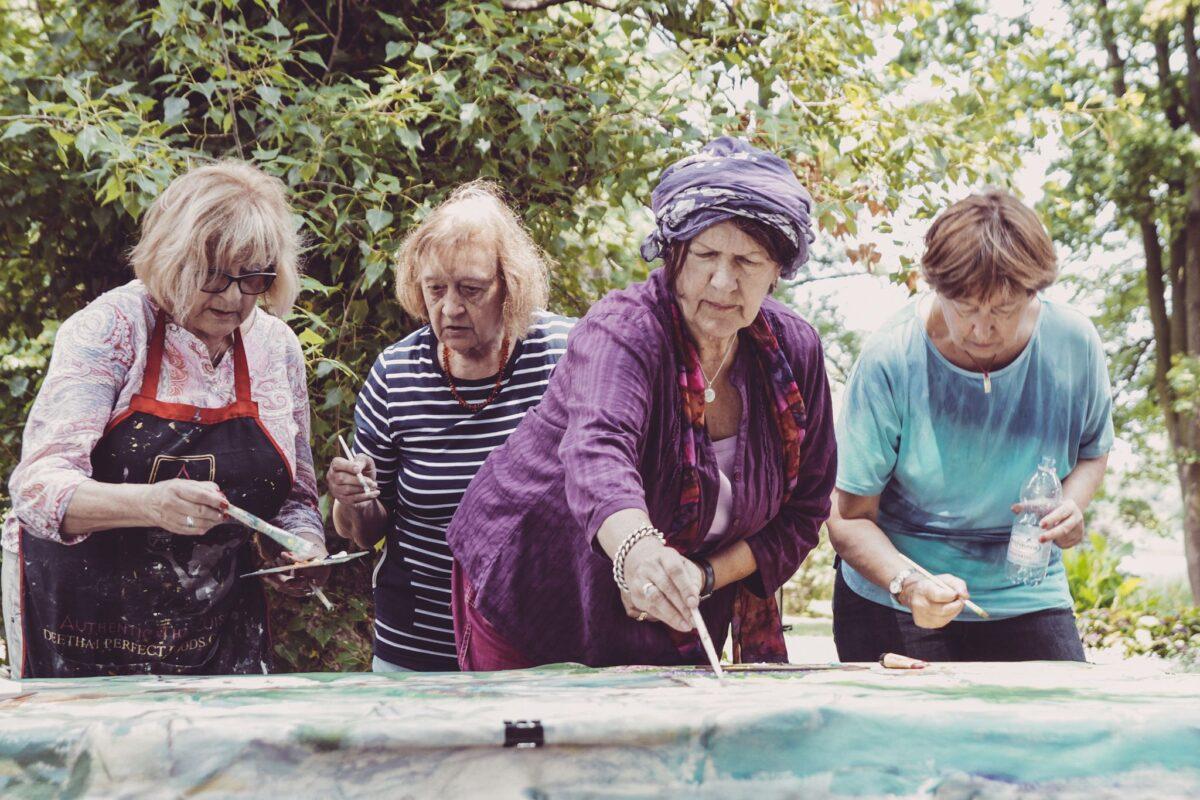 Cztery starsze kobiety pochylają się nad obrazem, który malują