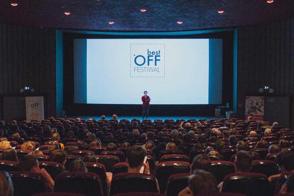 Zdjęcie przedstawia salę kinową. Na ekranie jest logotyp festiwalu Best Off. Na tle ekranu widzimy postać przemawiającą przez mikrofon.