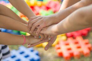 Zdjęcie przedstawia ręce dzieci, młodzieży - dłonie położone jedne na drugich