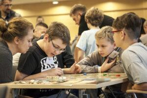 Na pierwszym planie grupa dzieci pochylonych nad grą planszową. W tle inni ludzie