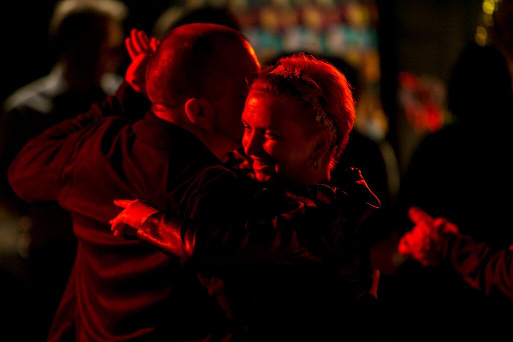 Zdjęcie przedstawia tańczącą parę. Widzimy twarz kobiety, jest uśmiechnięta.