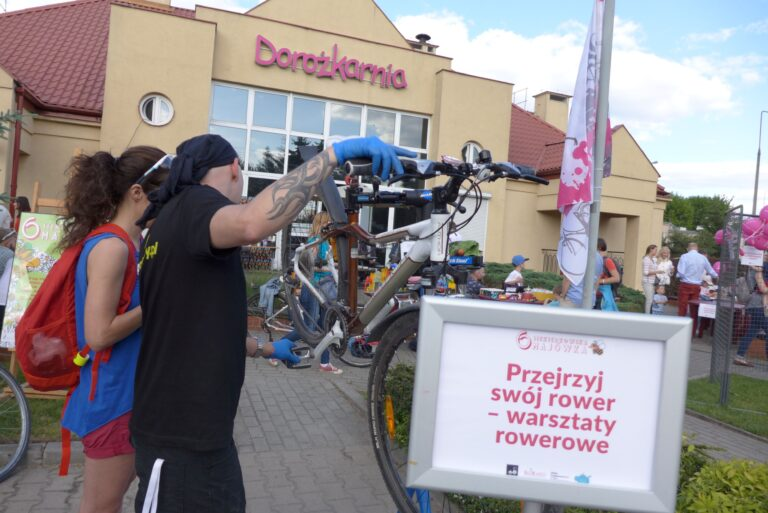 Zdjęcie przedstawia mężczyznę kobietę naprawiających rower. Stanowisko ustawione jest w plenerze, w tle budynek z neonem Dorożkarnia.
