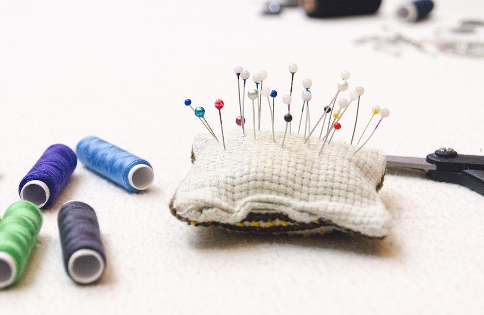 Zdjęcie przedstawia małą poduszkę, w którą wbite są szpilki krawieckie. Obok poduszki leżą szpulki nici.