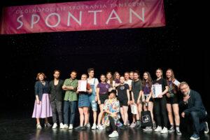 Zdjęcie przedstawia grupę młodzieży i dorosłych stojących na scenie. Nad nimi wisi napis Spontan.