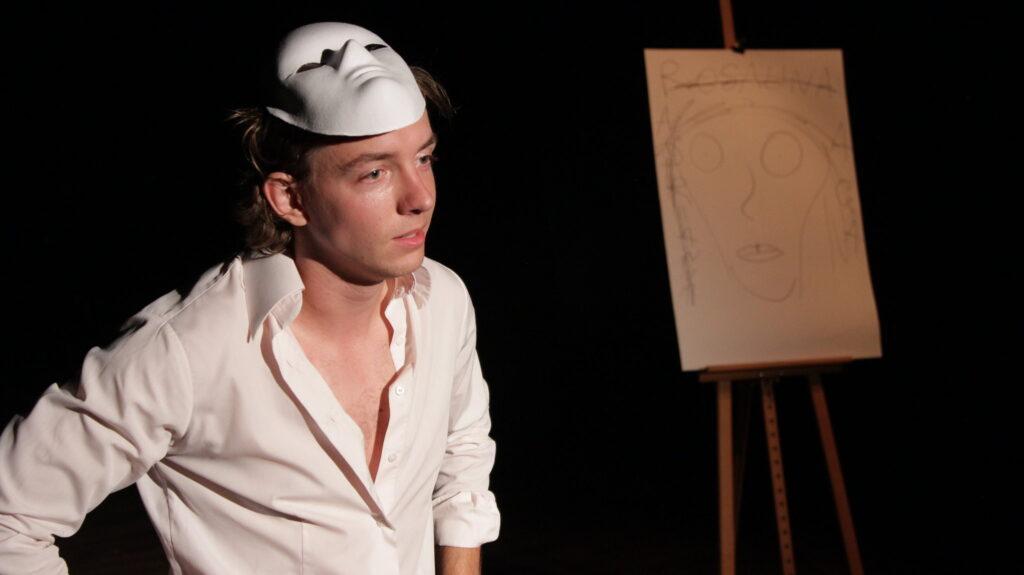 Zdjęcie przedstawia chłopaka na scenie. na głowie ma maskę teatralną.