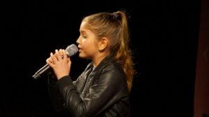 Dziewczynka z mikrofonem w dłoni, uczesana w koński ogon. Zdjęcie zrobione z profilu