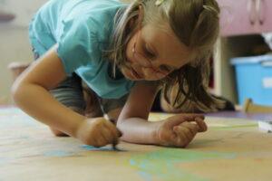 Kilkuletnia dziewczynka rysuje na płachcie papieru