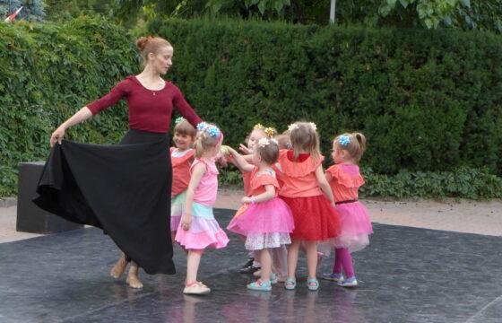 Zdjęcie przedstawia dorosłą kobietę oraz gromadę dzieci w wieku przedszkolnym. Kobieta tańczy, dzieci są z prawej strony kobiety.