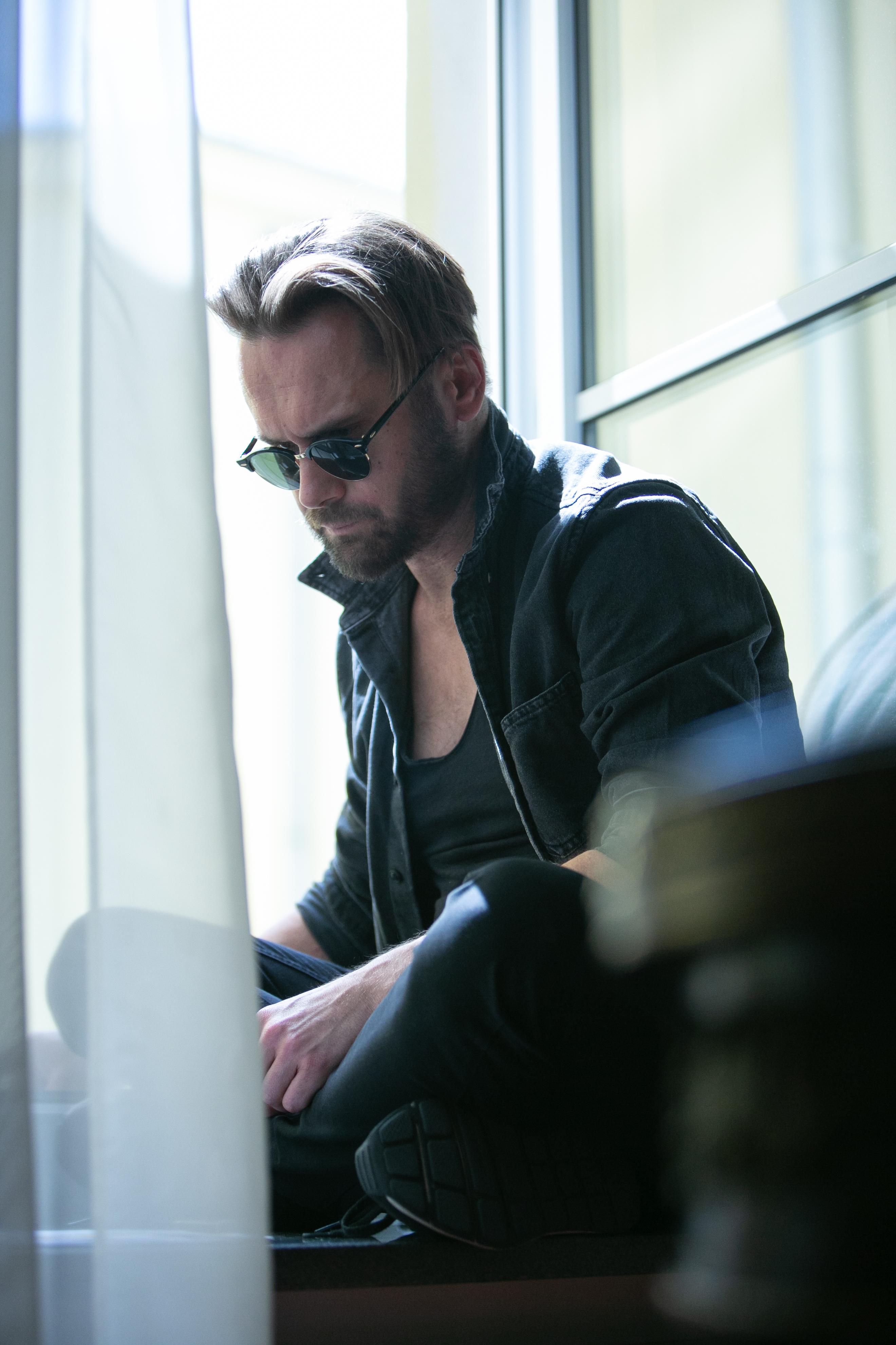 Zdjęcie przedstawia mżczyznę, siedzącego w otwartym oknie. Ma przeciwsłoneczne okulary.