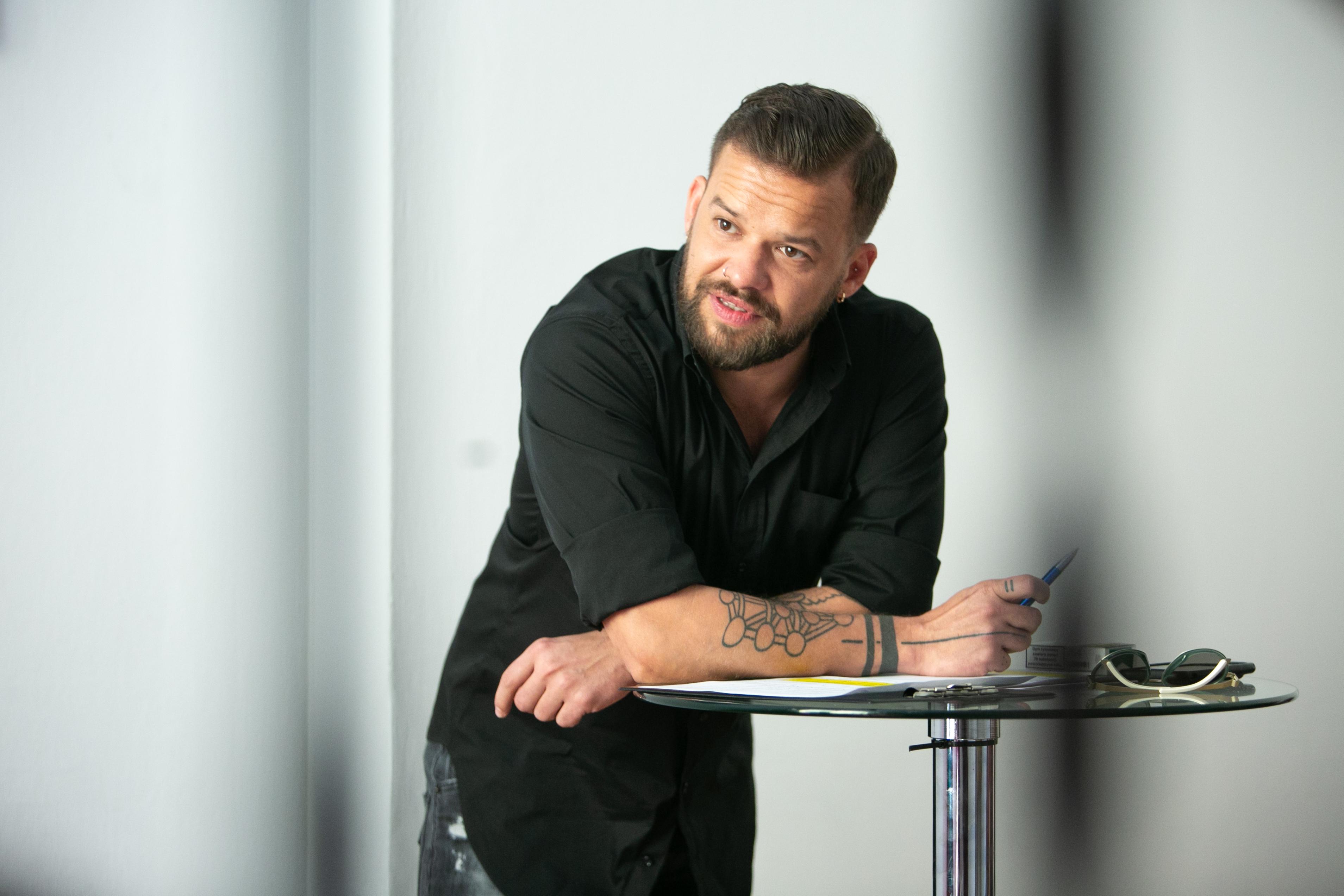 Zdjęcie przedstawia mężczyznę. Ręce ma oparte na stoliku. Na rękach ma tatuaże.