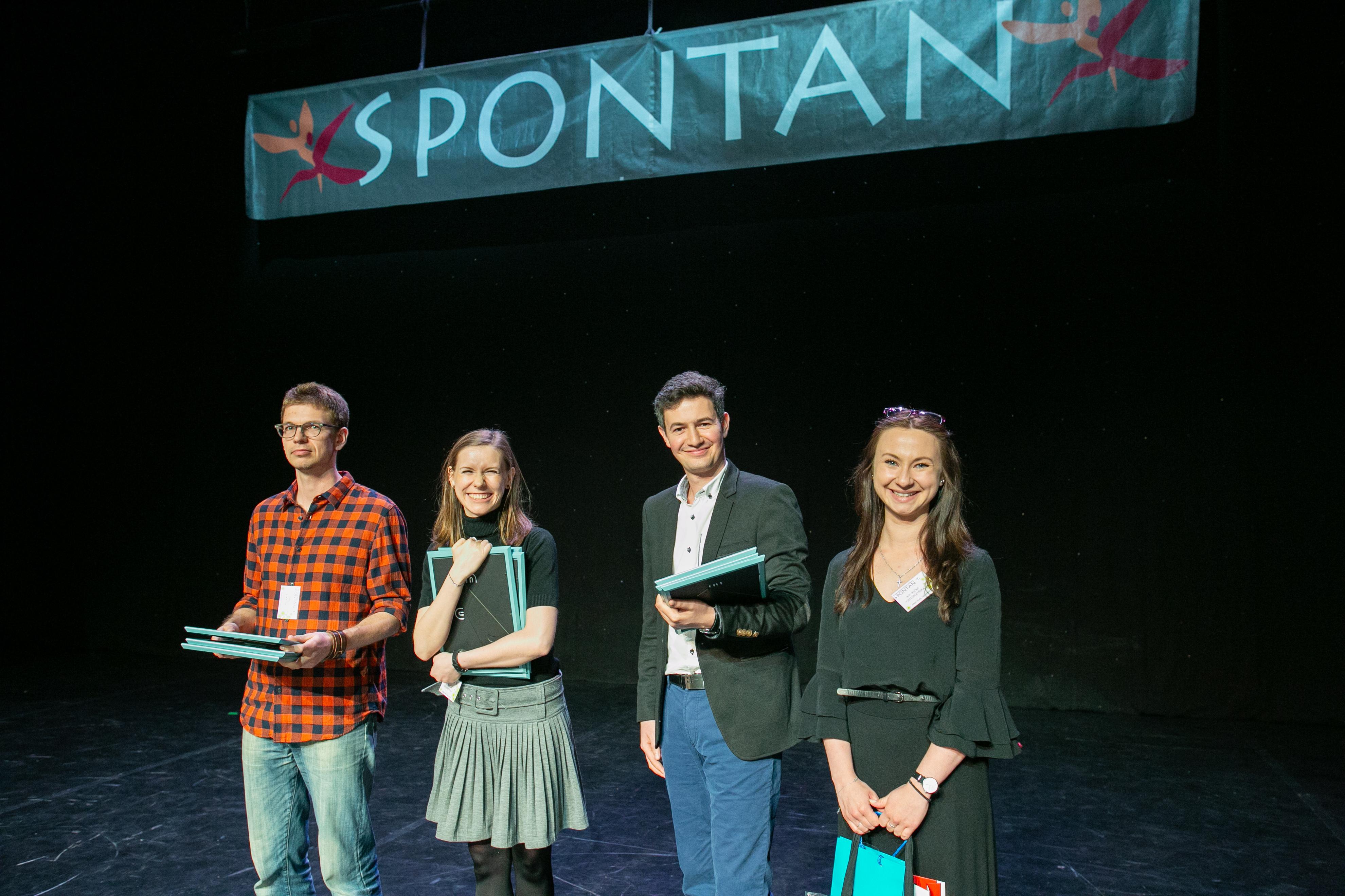 Zdjęcie przedstawia dwie młode dziewdczyny i dwóch młodych chłopców. Stoją na scenie pod napisem Spontan. Wszyscy się uśmiechają.
