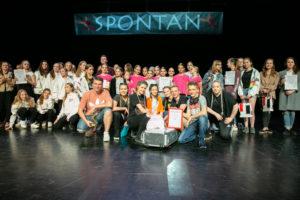 Zdjęcie przedstawia grupę młodych ludzi na scenie. Wszyscy stoją i siedzą pod banerem z napisem Spontan.