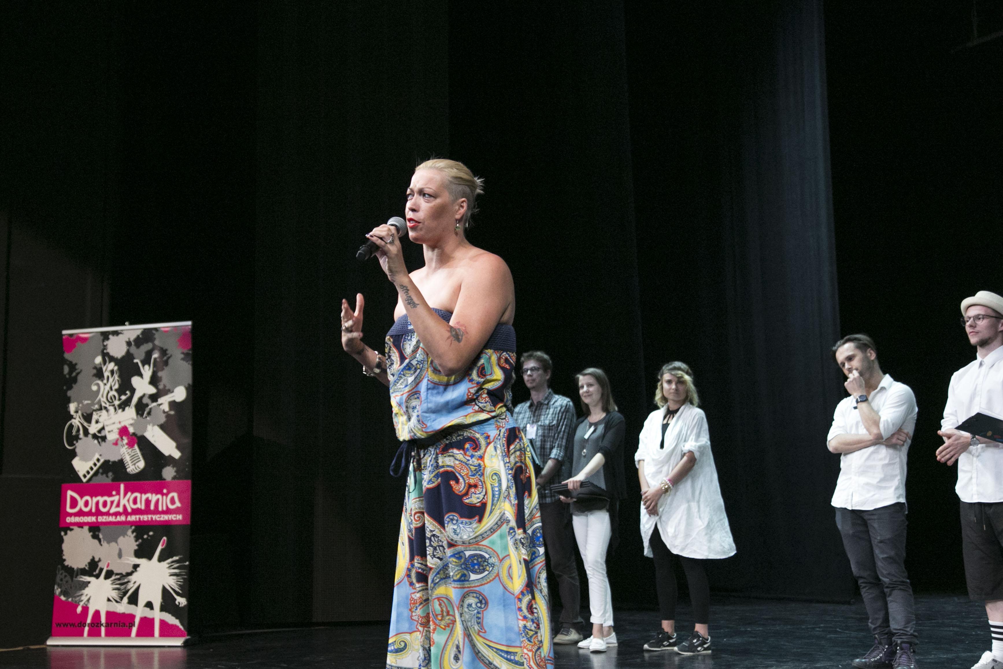 Zdjęcie przedstawia kobietę na scenie. W ręce trzyma mikrofon.