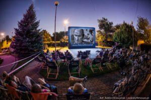 Zdjęcie przedstawia duży ekran kinowy ustawiony w plenerze. Przed ekranem ludzie siedzą na leżakach.