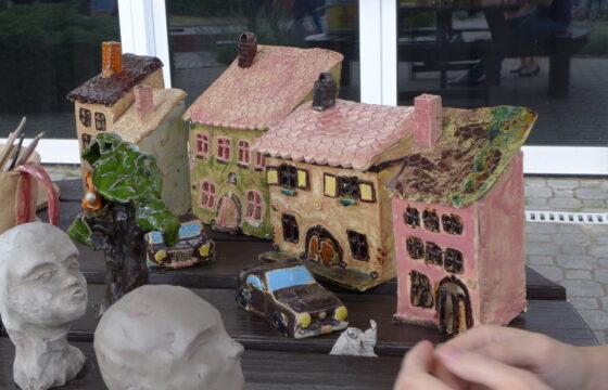 Zdjęcie przedstawia kilka prac wykonanych z gliny: 4 kamienice, auto, dwie głowy