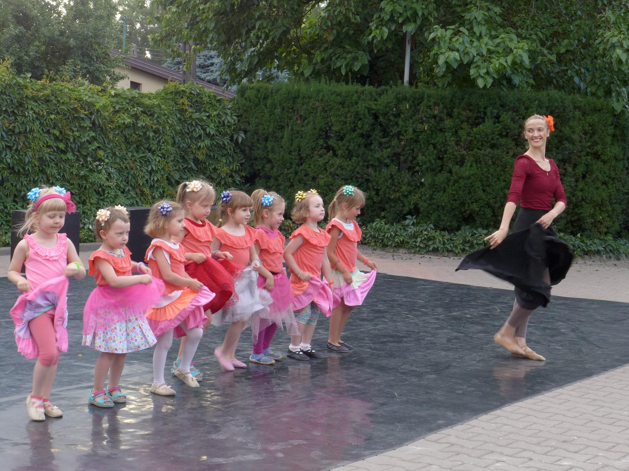 Grupa kilkuletnich dziewczynek na scenie w plenerze, Przed nimi młoda kobieta.