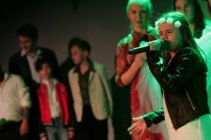 Zdjęcie przedstawia grupę dzieci na scenie. Dziewczynka na pierwszym planie trzyma w dłoni mikrofon.