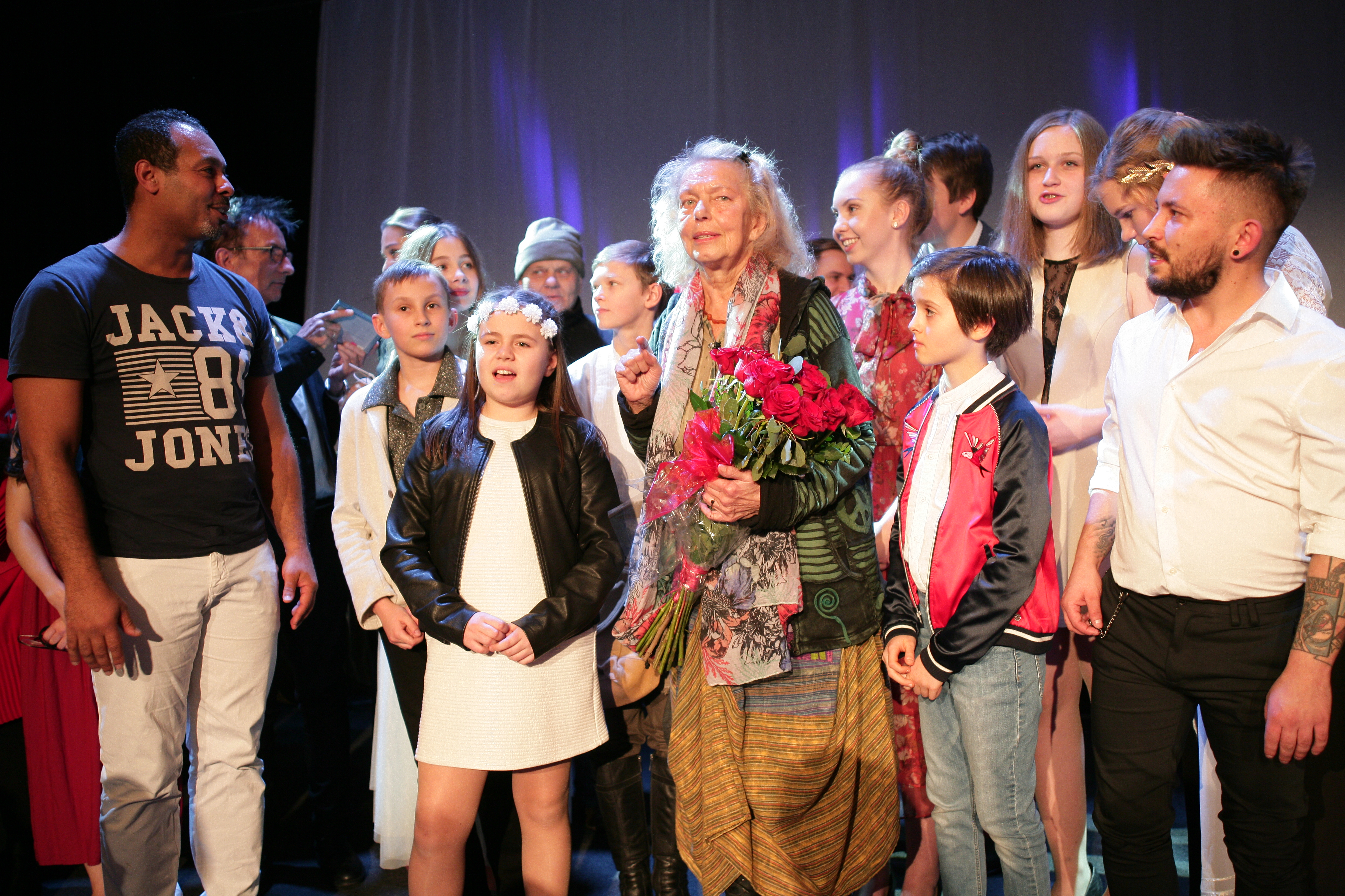 Zdjęcie przedstawia grupę ludzi na scenie. Starsza pani w środku grupy trzyma w rękach bukiet kwiatów.