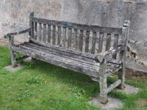 Zdjęcie przedstawia starą ławkę, najprawdopodobniej drewnianą.