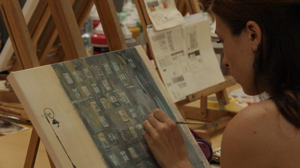 Profil dziewczyny pracującej przy sztaludze. Malarstwo.