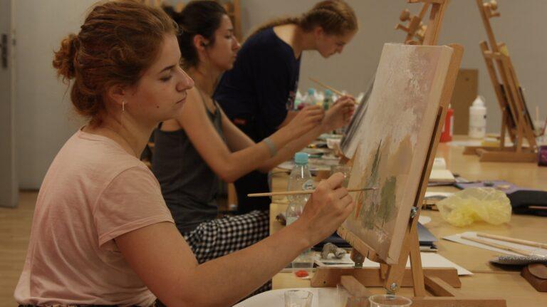 Trzy dziewczyny malujące na małych sztalugach. Sztalugi ustawione są na stołach.