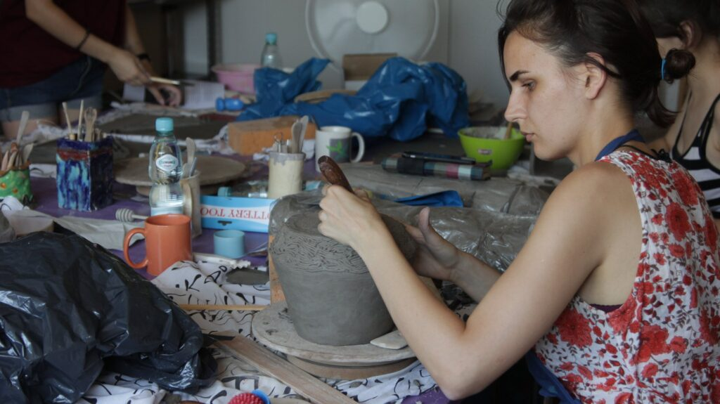 Pracownia plastyczna. Kobieta pracuje przy naczyniu najprawdopodobniej glinianym.