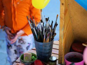 Zdjęcie przedstawia fragment stołu, na którym stoją przybory plastyczne. Na pierwszym planie kubek z pędzlami do malowania. W tle postać dziecka.