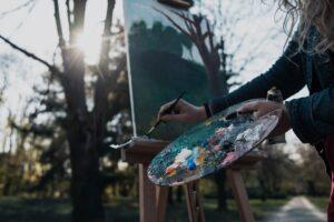 Zdjęcie przedstawia postać, która maluje farbami na obrazie ustawionym na sztaludze.