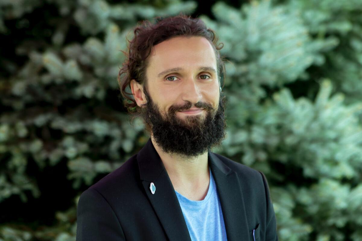Zdjęcie przedstawia młodego mężczyznę. Włosy ma zaczesane do tyłu, ma też brodę.